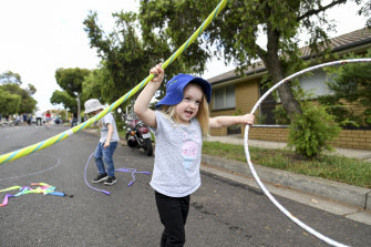Elise Duscio, 3, has a fine old time playing with hoops.