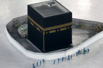 Workers disinfect the ground around the Kaaba, the cubic building at the Grand Mosque, in the Muslim holy city of Mecca, Saudi Arabia. The site is now closed.