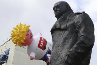 A blimp depicting Boris Johnson floats past a statue of Winston Churchill in London last month.