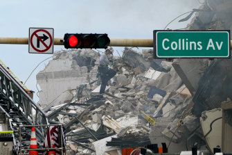 A rescue worker walks through the rubble of the 12-storey beachfront condo building.