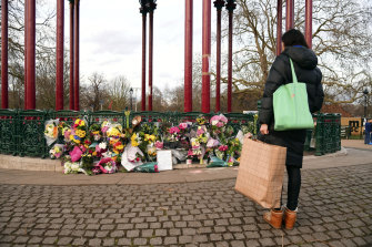 A woman stops to view flowers left at the bandstand on Clapham Common to mourn Sarah Everard.