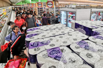People wait their turn to purchase toilet paper.