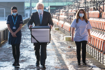 UK Prime Minister Boris Johnson carries doses of the COVID-19 vaccine.