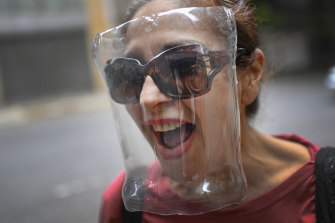 A woman wears a makeshift face shield made from a plastic bottle container as a precaution against the new coronavirus in Caracas.