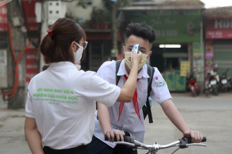 A student is scanned for temperature before entering Dinh Cong secondary school in Hanoi, Vietnam.