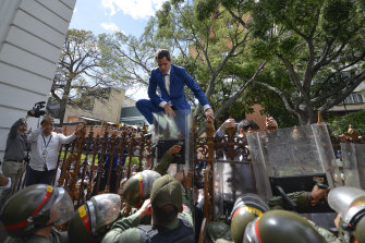 Venezuelan opposition leader Juan Guaido climbs a fence in an attempt to enter parliament.