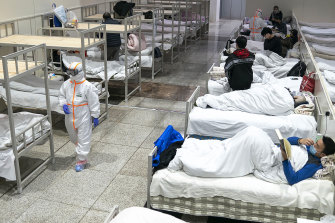 Patients diagnosed with the coronavirus settle at a temporary hospital set up in an exhibition centre in Wuhan.
