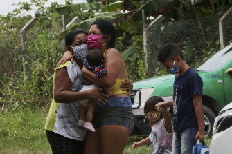 Relatives mourn at the roadside while awaiting the removal of the body of Arlen Bezerra, 39, a victim of COVID-19, in Manaus, Amazon state, Brazil.