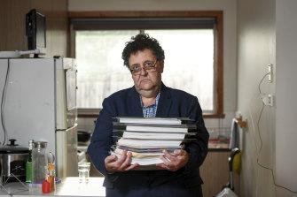 Davidh Digman in his Seaford, Melbourne home, holding his robo-debt files.