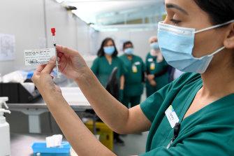 Western Health pharmacist Samira Hamidi prepares a coronavirus vaccine at the Melbourne Airport vaccination hub.