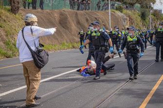 Age photographer Luis Ascui is pepper sprayed by a Victoria Police officer during the anti-lockdown protest in Richmond.