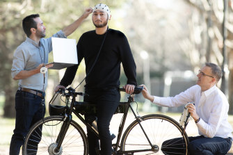 Researchers Josh Andres (left) and Floyd Mueller hook up cyclist Nathan Semertzidis to the intuitive technology.