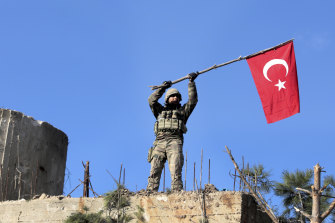 A soldier waves a Turkish flag as Turkish troops secure Bursayah hill, which separates the Kurdish-held enclave of Afrin from the Turkey-controlled town of Azaz, Syria.