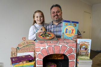 Wayne Murphy and his seven-year-old daughter Alexandra with the cardboard pizza oven they've made following instructions in a children's craft book.