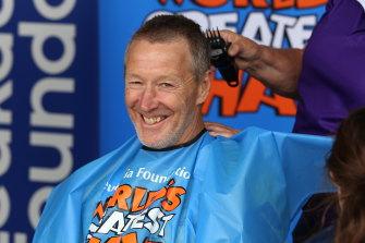 Bellamy smiles as he gets his hair cut.