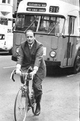 Transport Minister Milton Morris rides a bicycle from his office in Macquarie Street to a rally in Hyde Park North, 1974.