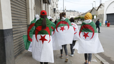 Demonstrators are draped in the Algerian flag during a rally in Algiers, on Friday.