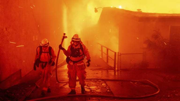 Firefighters battle the Camp Fire as it tears through Paradise.