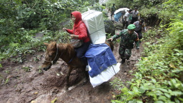 Officers escort electoral workers using horses to distribute ballot boxes and other election paraphernalia to polling stations in remote villages in Tempurejo, East Java, Indonesia.
