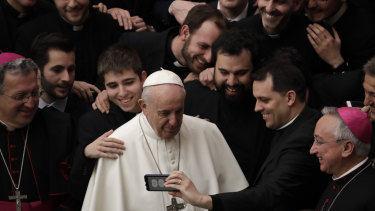 Pope Francis poses for a photo with a group of priests at the end of his weekly general audience on Wednesday.