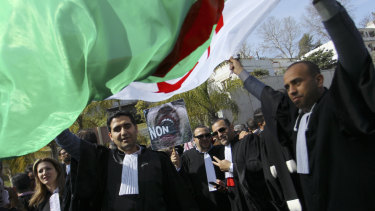 Algerian lawyers demonstrate with a national flag outside the constitutional council in a protest against President Abdelaziz Bouteflika.