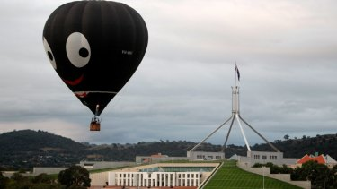 """The Black Magic hot air balloon, also known as """"Golly"""", is seen flying over Parliament House during the 2011 Canberra Balloon Spectacular."""