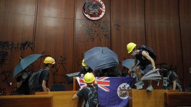 Protesters erect a Hong Kong colonial flag and deface the Hong Kong logo at the Legislative Chamber.