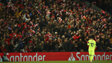 Lionel Messi walks in front of jubilant Liverpool fans after Liverpool scored their fourth goal.