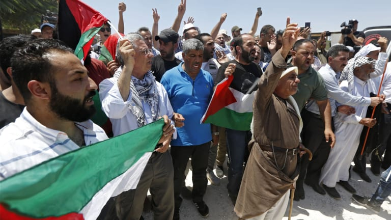 Palestinians hold flags during a protest in Khan al-Ahmar, last week.