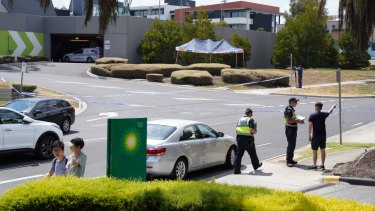 A woman's body lies under a tent as police question potential witnesses in Bundoora.