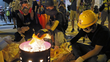 Protesters burn paper money to pay their respects for protesters who were injured on Aug 31 outside Prince Edward station in Hong Kong on Friday.