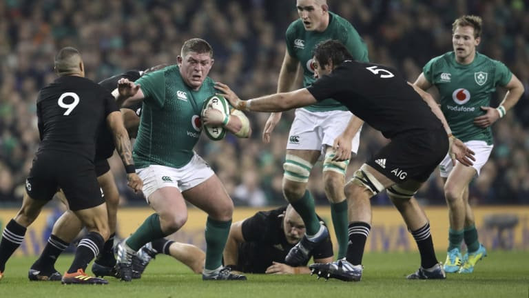 Ireland's Tadhg Furlong is tackled by New Zealand's Sam Whitelock and Aaron Smith (left).