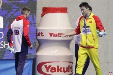 Gold medlaist China's Sun Yang, right, gestures to Britain's bronze medalist Duncan Scott.