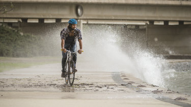 Robert Agostino from O'Connor rides home as strong winds whip up waves along the lake front in Parkes.