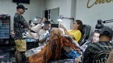 Dane Herden (left, standing) owner of Celebrity Ink Tattoo Bali studio watching his tattoo artists working.