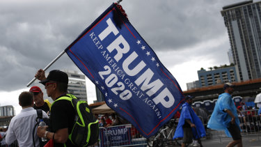 An attendee holds a campaign flag ahead of Trump's re-election launch in Orlando, Florida.