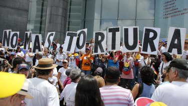 "People hold placards that spell out in Spanish: ""No more torture"" during an opposition protest against President Nicolas Maduro in Caracas last year."