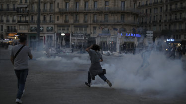 A protester runs among tear gas during a demonstration in Marseille.