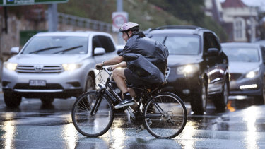 This Brisbane cyclist had to use a garbage bag for protection on Friday afternoon.