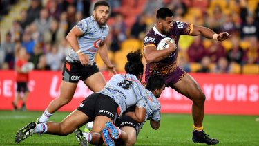 Payne Haas (right) of the Broncos gets past the Warriors defence to score a try in the round 17 draw at Suncorp Stadium.
