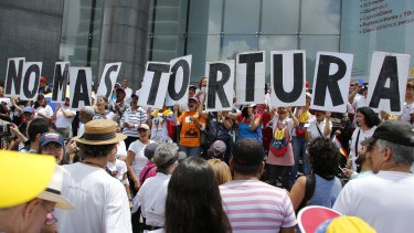 "People hold placards that spell out in Spanish: ""No more torture"" during an opposition protest against President Nicolas Maduro in Caracas on Friday."