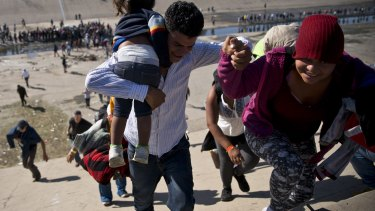 Migrants walk up a riverbank at the Mexico-US border after getting past a line of Mexican police.