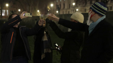 People raise a glass and celebrate in Parliament Square as the bell known as Big Ben strikes 2300, and Britain ends its transition period and formally leaves the European Union in London.
