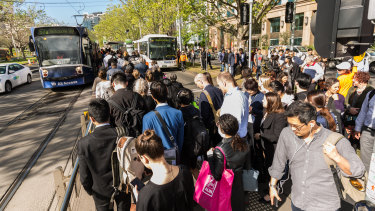 Commuters waiting for tram replacement buses along St Kilda Road, near the Shrine of Remembrance.