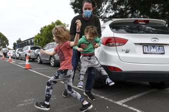 Michael Glen from Cheltenham with his boys Nate, 6, and Rocky, 4, play chasey while waiting for a COVID test in Parkdale.