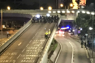 Tong Hua, 58, in his wheelchair speeding away from riot police on Harcourt Road.