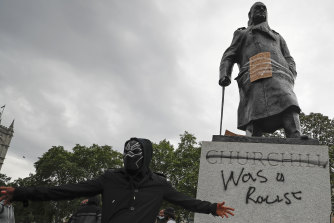 "Protesters hung a sign and painted ""racist"" on the Winston Churchill statue in Parliament Square during the Black Lives Matter protest rally in London."