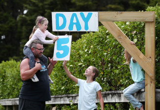 The Paddison family updates their roadside isolation countdown sign in Kaipara Flats, Auckland, on Tuesday.