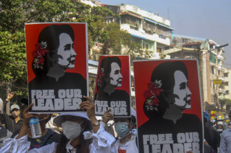 Anti-coup protesters display pictures of deposed Myanmar leader Aung San Suu Kyi in Yangon on Tuesday.