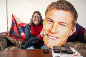 Demons cheer squad member Suzanne Considine celebrates her team's win while watching at home.